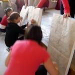 Uczniowie rysują na arkuszach papieru