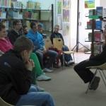 Autorka siedzi i tłumaczy młodzieży swoją pracę