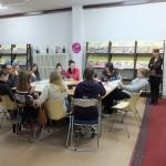 Młodzież przy stole słucha nauczyciela