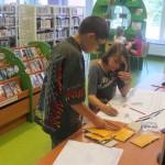 Dwójka dzieci rysuje przy stole na dużym arkuszu papieru