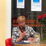 Jedna z uczestniczek czyta książkę trzymając mikrofon