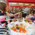 Młodzież i idzieci zgromadzone wokół stołu ze smakołykami