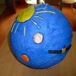 Niebieska kula, na niej słońce, planety i sztuczny satelita
