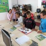 Dzieci oglądają rozłożone na stole książki o tematyce piłkarskiej