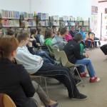 Młodzież siedzi i słucha wypowiedzi autorki