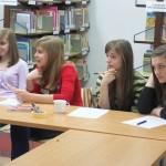 Cztery dziewczynki siedzą przy stole i słuchają wykładu