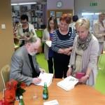 Autor podpisuje książki gościom