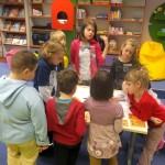 Dzieci zgromadzeni wokół stołu wykonują komiks na dużym arkuszu papieru