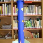 Niebieska rakieta z papieru, na niej kolorowe kółeczka
