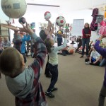 Dzieci podrzucają piłki do góry