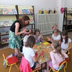 Dzieci przy stole wykonują laurki, pomaga im pracownik biblioteki
