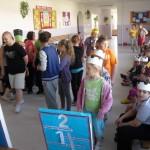 Uczniowie uczestniczą w zajęciach, część z nich ma na głowie papierowe korony