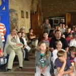 Dzieci i doroścli siedzą na sali zamku