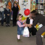Bibliotekarka wręcza nagrodę lauratowi konkursu