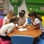 Cztery dziewczynki siedzą wokół stolika i przyklejają obrazki do kartki