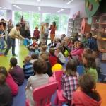 Dzieci siedzą i słuchają twórców, jedna autorka podaje dziecku podaje dziecku zabawkę do obejrzenia