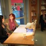 Aktorki grają siedząc przy stole oświetlonym przez lampkę biurkową