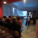Goście oglądają na ekranie pokaz zdjęć obrazujących bibliotekę przed i po remoncie