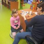 Pracownik biblioteki maluje twarz dziewczynce