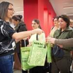 Pracownik biblioteki wręcza gościom torebki z upominkami