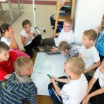 Dzieci piszą na dużym arkuszu papieru ułożonym na podłodze