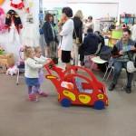 Dziecko pcha wózek w kształcie samochodu