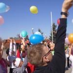 Dzieci przed szkołą wypuszczają balony
