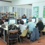 Seniorzy siedzą przy stołach z komputerami