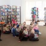 Dzieci siedzą na podłodze i oglądają prezentację