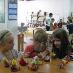 Dzieci oglądają przez lupę przedmioty w bibliotece