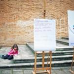 """Sztaluga z planszą, na której napisano """"Czytanie dla umysłu jest tym, czym ćwiczenia fizyczne dla ciała"""", w tle dziewczynka na schodach spożywa zupę"""