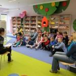 Dzieci siedzą i słuchają wypowiedzi bibliotekarki
