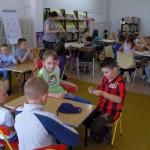 Dzieci w grupach wykonują zadania zlecone przez prowadzącą