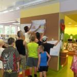 Pracownicy biblioteki wieszają na ścianie wykonane prace, dzieci pomagają