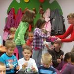 Jedna z autorek rozdaje dzieciom lizaki
