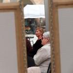 Goście słuchają recytacja, widok uczestników spomiędzy ram obrazów