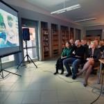 Goście i pracownicy biblioteki oglądają film na ekranie