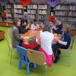 Dzieci siedzą wokół stołu i wykonują prace ręczne