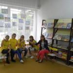 Pięcioro uczestniczek projektu siedzi przy regale z czasopismami