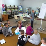 Dzieci siedzą na podłodze, jedno z dzieci siedzi przy flipcharcie