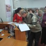 Uczestnik spotkania wpisuje się do księgi pamiątkowej