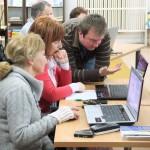 Prowadzący pomaga starszym paniom wykonać zadania na komputerze