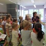 Bibliotekarka na flipcharcie przygotowała zadanie, dzieci stoją w pobliżu i przyglądają się