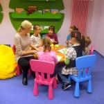 Sześcioro dzieci i jedna osoba dorosła siedzą przy stoliku i wykonują prace ręczne