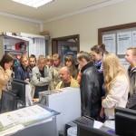 Uczestnicy przyglądają się pracy dziennikarza na komputerze