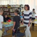 Dzieci przy stole wykonują laurki, przy nich stoi wychowawczyni