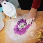 Pokaz tworzenia rękodzieła przez autorkę, na stole element przypominający kwiat, autorka plewa go gorącą wodą z czajnika