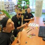 Trzej chłopcy przy stole wykonują pracę z plasteliny