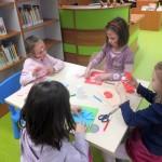 Cztery dziewczynki siedzą przy stoliku i wyklejają