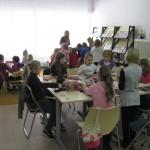 Dzieci sprzy stołach wykonują prace plastyczne